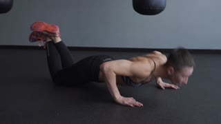 Sporty woman doing push-up exercise. The woman is actively pushing herself off the floor, leaning on her knees and crossing her legs.