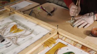 Stained-glass master is preparing a parts for glass painting. Woman is cutting leaf by small cutter and breaking off a pieces by pliers