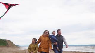 Steadicam shot of cheerful family walking on the coast on windy chilly day. Dad carrying little daughter, boy flying a kite