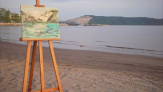 Still life, painted on canvas, stands on an easel next to the coastline near the sea or the river, A beautiful picture in the style of impressionism painted in oil