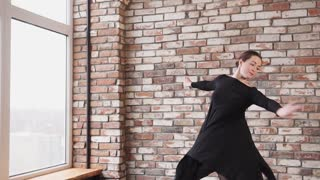 Student of dancing school is training in a hall. She has very plastic body, she is bending