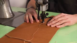 Tailor is stitching by sewing machine leather goods. Man is directing skin details under a needle, finishing, cutting out threads.