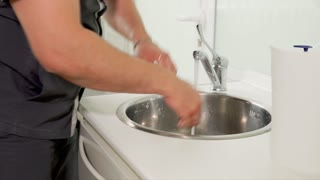 The adult doctor carefully washes his hands under the water in the sink before putting on latex gloves and proceeding to examine or treat the patient.