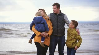 The adult spouse and his wife are standing with a small child in their arms and grown up by an adult son near the sea and enjoying a day off, this is a friendly and joyful family