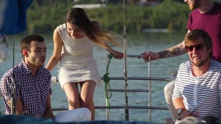 The alumni company celebrates a vacation on a modern boat, classmates communicate on a yacht in the evening, men and women are beautifully dressed and enjoy the evening sunset in the summer