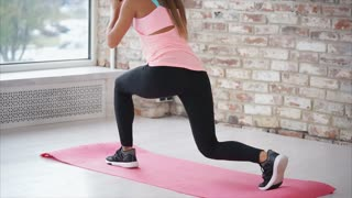 The athletic woman makes attacks on one leg, the lady performs strengthening and stretching exercises for the muscles of the buttocks and legs, she makes active movements