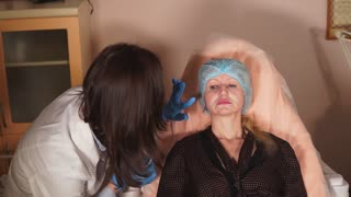 The beautician at the hospital checks whether the recent ointment of anesthesia affected the middle-aged woman who came to make injectable implants, for anti-aging