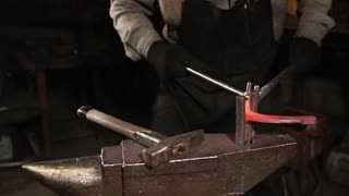The blacksmith is bending red hot iron holding big metal tongs in a forge. He is putting a lot of pressure on iron.