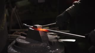 The blacksmith is working with red hot iron and a molder in a forge. He is forming hot iron for further work.
