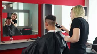 The blonde hairdresser cuts her hair with an electric razor, a man who came to a beauty salon and sits in front of a mirror expects a change of image and good service