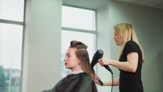 The blonde hairdresser dries long hair with the help of a warm air dryer and comb, a woman who came to the beauty salon expects a change of image and good service
