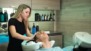The blonde hairdresser washes the head of the man with shampoo, the hair stylist is massaging to make the client enjoy the service and service of the fashion spa center