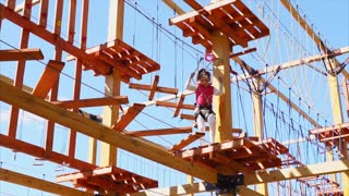 The child walks on the hanging park, the girl steps over the wooden steps and deftly copes with the obstacles, it is secured with the help of an insurance cable