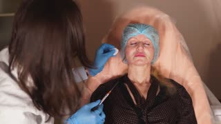 The cosmetologist of a private clinic disinfects the woman's skin to make injectable implants with the help of a cannula needle. The doctor anesthetized the skin, the infection does not get caught