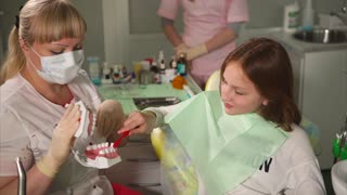 The dentist tells the teenager how to properly brush his teeth, the girl and the doctor together try to hold and drive with a brush on the plastic teeth