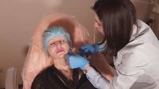 The doctor of a private clinic leads a preparation on the basis of hyaluronic acid with a cannula needle. The patient wants to rejuvenate the face, get a lifting effect