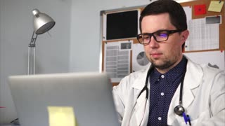 The doctor of a private clinic who wears a white robe, on the neck of a stethoscope, prints the text on the laptop in his personal cabinet. A man with poor eyesight looks at the monitor.