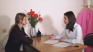 The doctor of the private clinic collects an anamnesis about the patient for future treatment. The therapist fills the questionnaires for treatment, the middle-aged woman listens attentively.