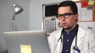 The doctor wearing eyeglasses and a white robe, with a stethoscope on the neck, typing the text on the laptop in his personal cabinet.