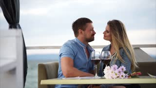 The husband and wife celebrate their anniversary in a restaurant near the water, a man and a woman drink wine in a cafe, a couple in love are happy with each other and talking