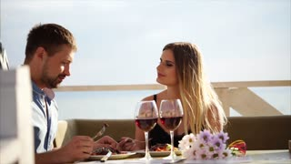 The husband and wife celebrate their anniversary in a restaurant near the water, a man feeds his woman an appetizing dinner in a cafe, a couple in love eating and drinking wine