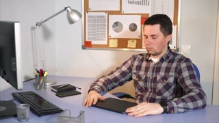 The man who sits behind the workplace holds his hands to his head, he has a headache. A man worked hard in the office, using a mobile phone, tablet, computer, now he needs a break and rest