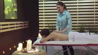 The massage therapist does the relaxing massage with coconut cream to the girl with dark hair who is in Spa. Near a massage table there are aromatic candles, that can help to the client have a rest.