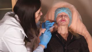 The patient of the beauty salon makes treatment with botox injections to get rid of facial wrinkles in the area of the lips. A woman wants to get rid of wrinkles and give the skin an anti-aging effect