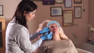 The plastic surgeon of the private clinic applies pain medication on the face of a middle-aged woman to make an injection against wrinkles, this will make the skin lift and rejuvenate her