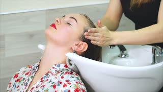 The process of washing the head in the beauty salon, the hairdresser uses shampoo to clean the long hair of the beauty salon, the woman who came to change the image lies with her eyes closed