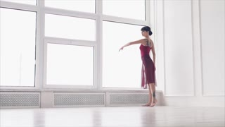 the teacher on the choreography puts the number for the performance on the stage, the lady trains the movements during the dance and gracefully lifts her hands upwards
