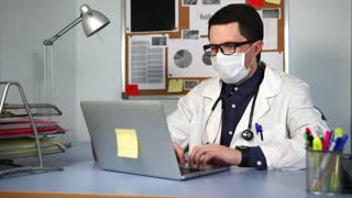 The therapist sits in his office in the clinic and uses a computer to make an anamnesis. A man in a white coat with a stethoscope looks at the computer monitor and thinks about treating the patient