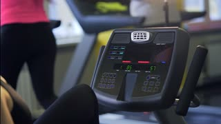 The woman changes the program on the running simulator, where she also can see how long the person practiced on the simulator, how many calories burned.