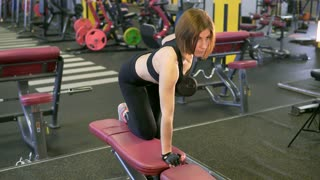 The woman lifts the dumbbells in a half-bent position, leaning on the knee and arm, keeping her back straight and not straining her lower back. This is for the development of muscle mass.