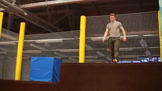 the young man is engaged in sports jumps, the person is in the trampoline center, the athlete jumps from the springboard to the trampoline making coups in the air