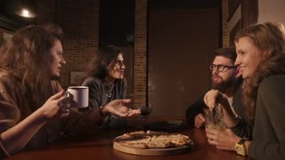 Three women and on man sitting together at the table in a nice bar. They are having fun, telling stories and drinking cocktails. Pizza on the table.