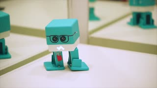TOGLIATTI, RUSSIA - JULY 21, 2017: Little cubic funny turquoise robot walking and dancing. Plastic robot with drawn glasses and tools. In exhibition City of Robots in the Mall Park House.