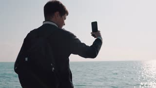 Traveler is filming calm seascape in sunny day, standing back to camera. He is holding mobile phone in hands and moving it, solar path on a sea surface