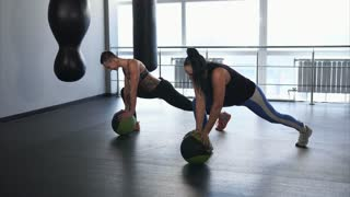 Two adult women do exercises to stretch the gluteus muscles and the back of the thighs in the fitness club. Athletes use a ball to support it with their hands, lunges forward make the muscles stronger