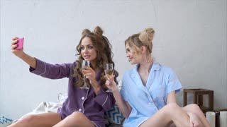 Two attractive women having fun. Drinking wine and making selfie together. Concept of hen-party.