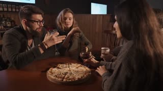 Two beautiful couples meet in a restaurant. They are eating pizza drinking alcohol and telling stories.