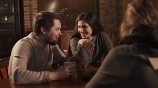 Two couples meet together in a restaurant and sitting at the table. They are laughing and talking.
