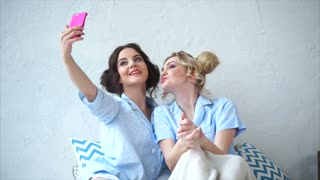 Two female friends doing selfie together. Concept of friendship. Pajamas party.