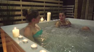 Two friends share their impressions of staying in an expensive spa center. Girls are sitting in a jacuzzi with water bubbles, the bath contains sea salt for moisturizing and skin mineralization.
