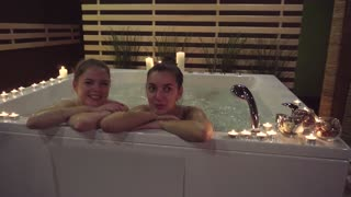 Two happy girls who came to get a spa treatment, enjoy a jacuzzi. Girls spend time in the water with aromatic oils, which moisturize the skin. Romantic atmosphere, candles, nice music help to relax.