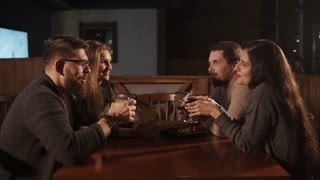 Two men and women are having fun together in a bar. They are drinking cocktails and talking happily.