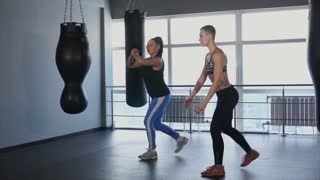 Two sporty woman do synchronous exercises for development of the gluteal muscles and the muscles of the hamstrings. Women practise fitness sport to maintain their physical form and active lifestyle.