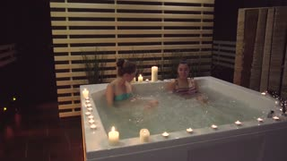 Two women are talking in the whirlpool with water bubbles about the spa treatments that they can get in the spa center. Women want to make their skin softer, fit and younger