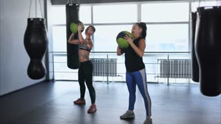 Two women go in for sports at the fitness club. Athletes do squats with a heavy ball, then lifting the ball over his head, doing exercises on the buttocks and strengthening the muscles of the hands.