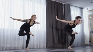 Two women practice yoga in the class. They do exercises called asanas.